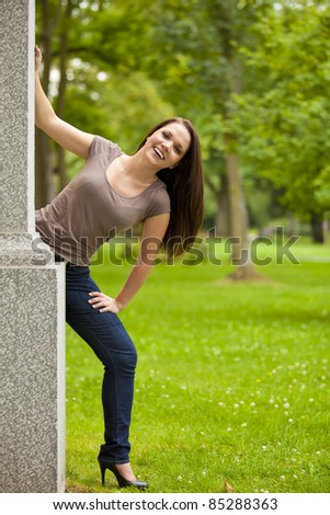 laughing beautiful brunette woman standing outside a building in a park