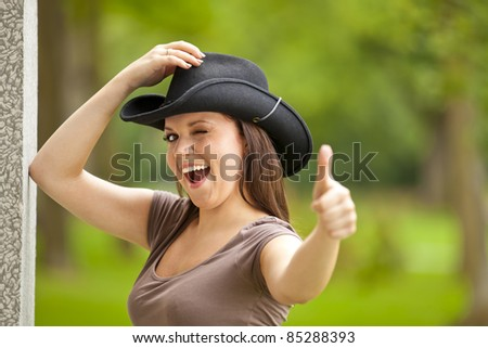 laughing beautiful brunette woman with a cowboy hat standing outside a building in a park and posing thumbs up