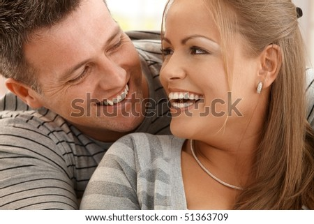 Laughing beautiful couple looking happily at each other in closeup.