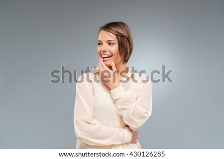 Laughing beautiful girl looking away isolated on the gray background - stock photo