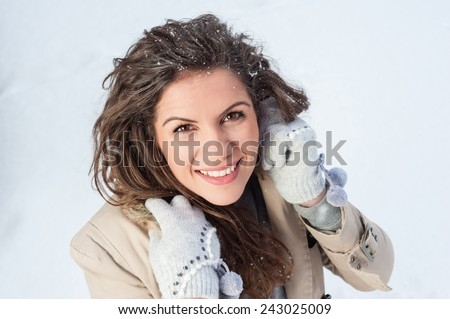 Laughing beautiful girl portrait in winter time with snow.