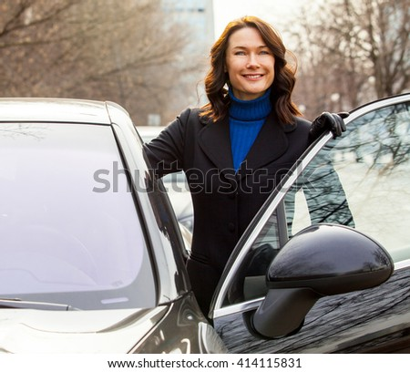 laughing beautiful middle-aged woman sits in the car - stock photo