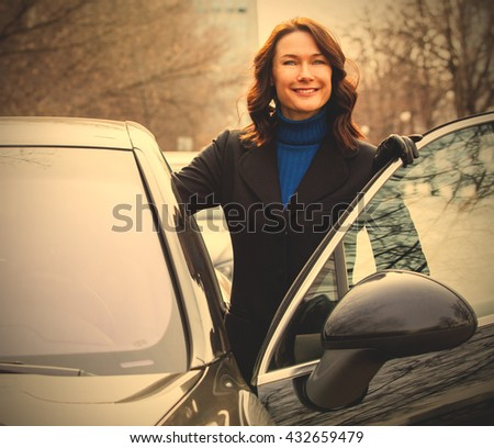laughing beautiful middle-aged woman sits in the car. instagram image filter retro style - stock photo