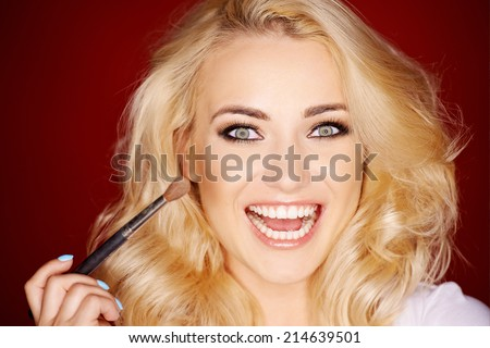 Laughing beautiful woman applying blusher to her cheek with a large cosmetic brush as she glances sideways at the camera - stock photo