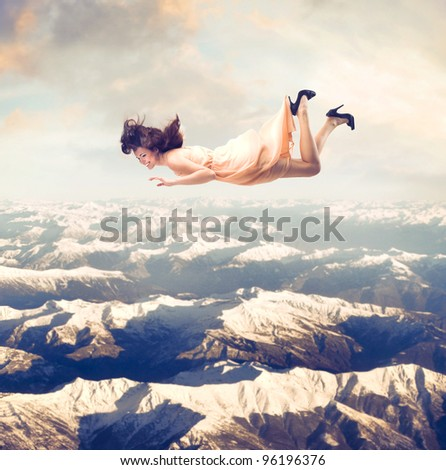 Laughing beautiful woman flying over the mountains - stock photo