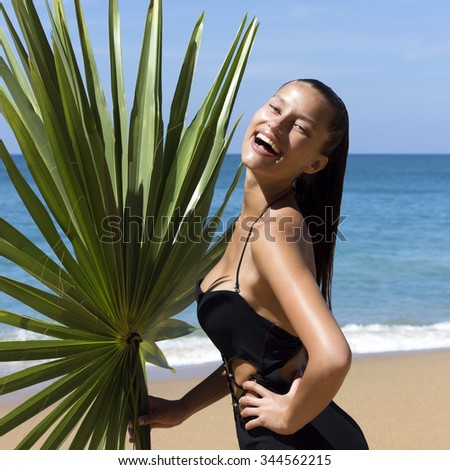 Laughing beautiful woman in bikini with palm branch on beach near sea enjoying sun. Hair up.Tropics.Hot summer day.Sexy girl.Vacation.Photo from Phuket island. Thailand - stock photo