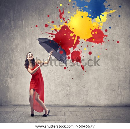 Laughing beautiful woman using an umbrella as a shelter against color drops falling down - stock photo
