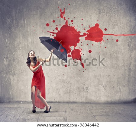 Laughing beautiful woman using an umbrella as a shelter against red paint drops falling down - stock photo