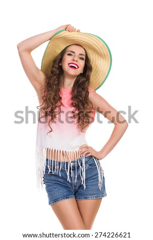 Laughing beautiful young woman in jeans short, pink top and straw hat. Three quarter length studio shot isolated on white. - stock photo