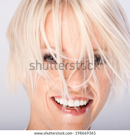 Laughing beautiful young woman with funky blond hair hanging in wisps all over her face , close up face portrait