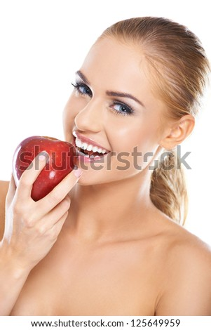 Laughing blonde woman with bare shoulders holding a large ripe red apple in her hand in a depiction of healthy eating - stock photo