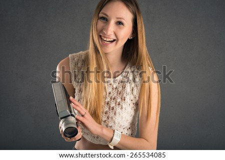 Laughing blonde woman with vintage film camera close up against dark grunge background.