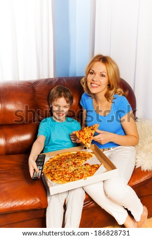 Laughing boy and mother eating pizza on the sofa - stock photo