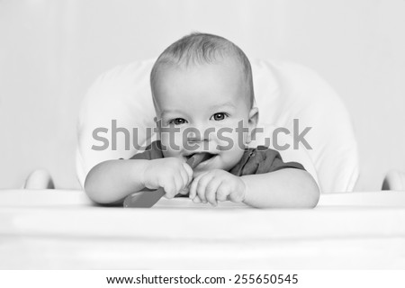 laughing boy holding a spoon on a white background  ( black and white ) - stock photo