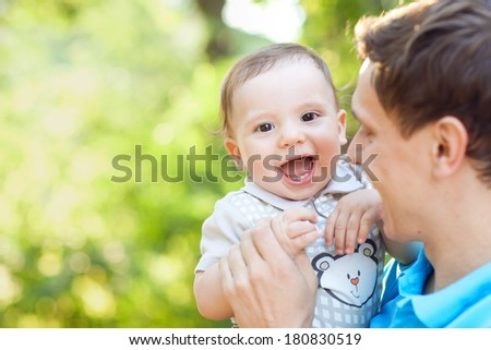 laughing boy in fathers hands - stock photo