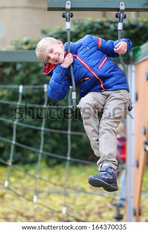 Laughing boy in warm blue bright coat having fun at the playground climbing on the net on a late autumn day  - stock photo