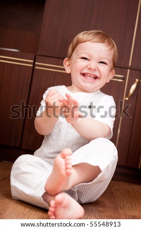 Laughing boy is sitting on wooden floor - stock photo
