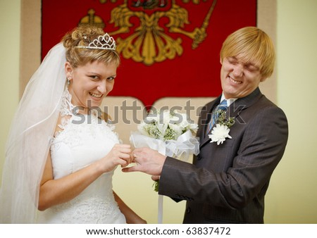 Laughing bride and groom wear a ring - stock photo