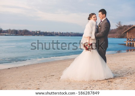 laughing bride with groom on the beach - stock photo