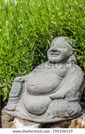 laughing buddha statue, in front of lavender bush - stock photo