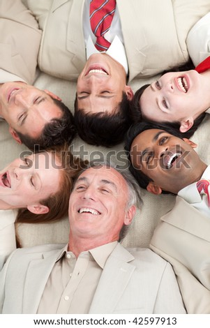 Laughing Business team lying in a circle with heads together - stock photo