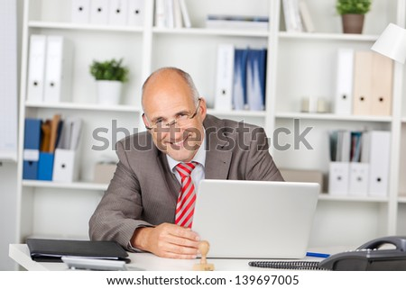 laughing businessman looking at the side of laptop - stock photo