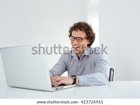 Laughing businessman working on laptop computer in office - stock photo