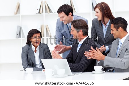 Laughing businesswoman applauded by her team in the office - stock photo