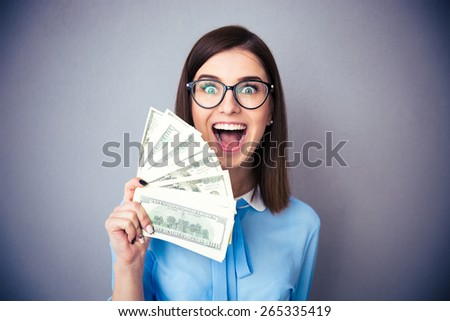 Laughing businesswoman holding bills of dollar and shouting over gray background. Wearing in blue shirt and glasses. Looking at camera - stock photo