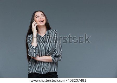 Laughing businesswoman talking on the phone over gray background - stock photo