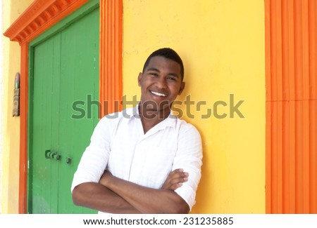 Laughing caribbean guy in front of a colorful house - stock photo