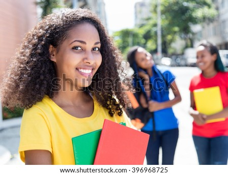 Laughing caribbean student in the city with friends - stock photo