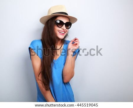 Laughing casual female in fashion sun glasses and summer hat on blue background