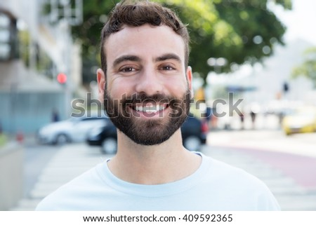 Laughing caucasian man with beard outdoor in city - stock photo