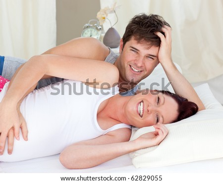 Laughing caucasian pregnant woman lying on bed with her husband in the bedroom - stock photo