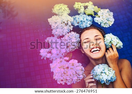 "laughing caucasian woman in a pool full of flowers. ""Instagram"" style filter applied - stock photo"