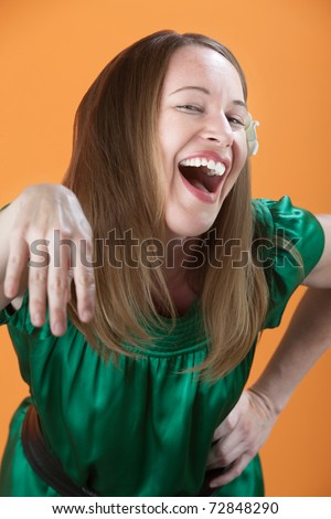 Laughing Caucasian woman sticks her hand out - stock photo