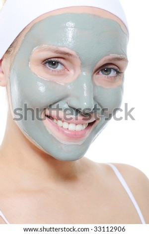 laughing cheerful female face with cosmetic mask of clay on it - stock photo