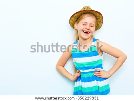 laughing child girl portrait on white background. yellow hat . fashion style posing.