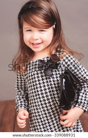 Laughing child girl 5-6 year old holding black leather bag in room. Childhood. Playful. Cheerful. - stock photo