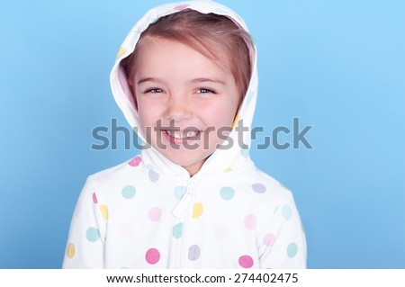 Laughing child girl 3-4 year old wearing hoodie with polka dots pattern over blue. Childhood. Positive emotions. Cheerful. Happiness.  - stock photo