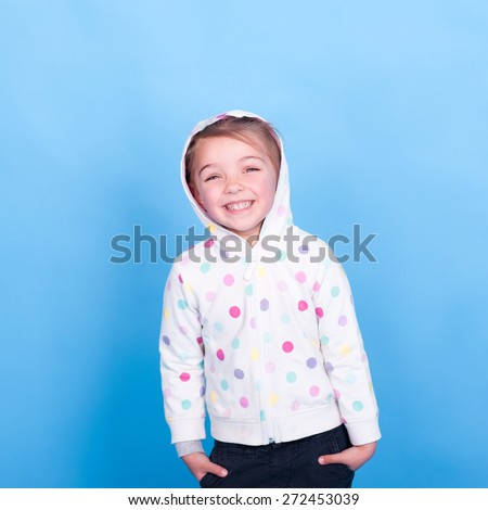 Laughing child girl 3-4 years old posing in room over blue. Wearing hoodie with polka dots. Hands in pockets. Looking at camera. Having fun.  - stock photo