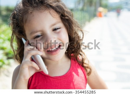 Laughing child in a red shirt speaking at phone outside - stock photo