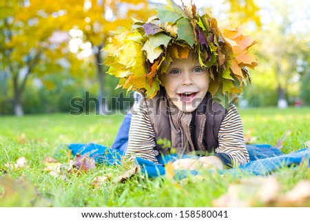 Laughing child lies on a grass in a wreath from maple leaves - stock photo