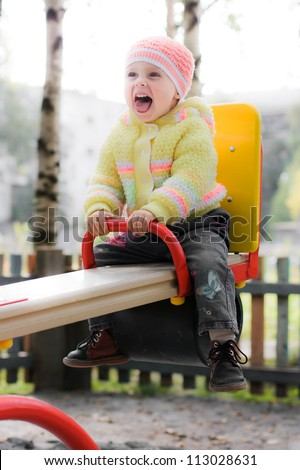 Laughing child on swing in autumn park - stock photo