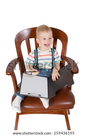 Laughing child sitting in an armchair and writes on a piece of paper attached to the folder isolated on a white background