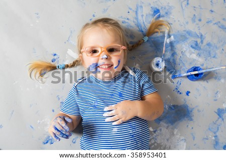 Laughing child with blue paint dots on face with colors and brushes lying on floor.