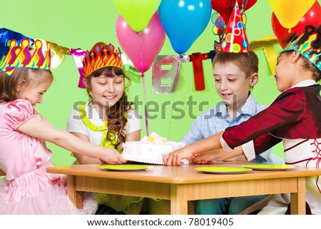 Laughing children fighting for the birthday cake - stock photo