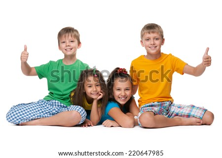 Laughing children hold their thumbs up on the white background