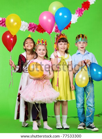 Laughing children holding balloons in hands - stock photo